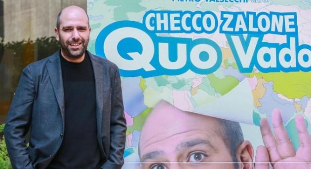 Checco Zalone davanti alla locandina di Quo vado?